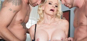 Mature blonde with fake tits Cammille Austin enjoys two cocks in anal and cunt