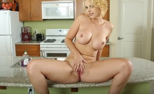 Blonde MILF with short hair reveals her big juicy tits and twat in the kitchen
