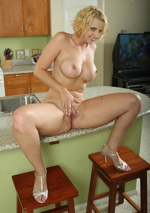 Blonde MILF with silicon boobs drills herself with a big dildo in the kitchen
