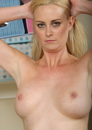 Middle aged blonde lady Camryn undresses to pose naked in laundry room