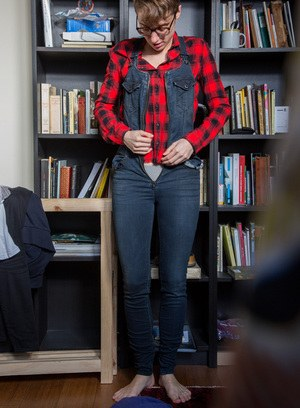 Skinny amateur Gretchen dresses herself among library stacks