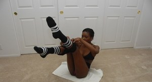 Sporty ebony sweetie in socks plays a solo showing charming boobs and pussy