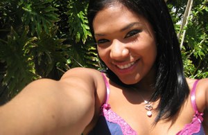 Smiling Latina babe Emy Reyes plays a clothed solo outdoors reveals hot curves