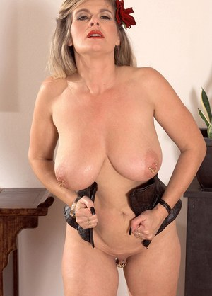 Bosomy mature housewife Marina Rene stuffs her pierced twat with a red dildo