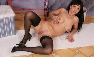 Middle aged brunette strips to black stockings before fingering her twat
