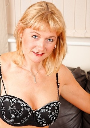 Mature blonde dame Suzy Wilde undresses for pussy play on leather couch