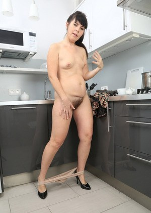 Mature brunette Malavi Mepanse licks her fingers after playing with her beaver