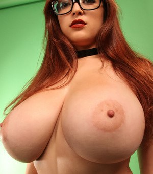 Redhead chick in glasses shows her marvelous huge boobs in a closeup shoot