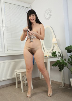 Mature brunette Malavi Mepanse strips off to play with her awesome hairy cunt