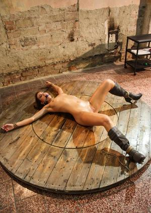 Gagged woman lies on the floor in a fixed position ready for BDSM treatment