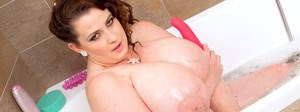 Fat brunette Anna Beck wets up her giant tits in shower before masturbating