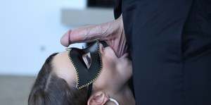 Brunette female Lily Love adorns a mask before giving a ball sucking blowjob
