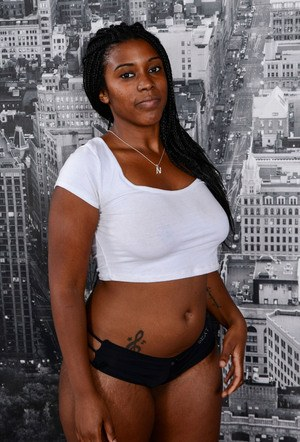 Ebony seductress Janelle Taylor exposes her medium-sized boobs and black pussy