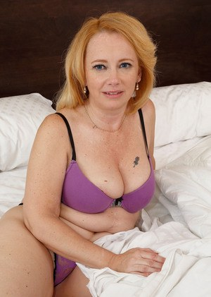 Sexy older lady Brandie Sweet spreads her pink labia lips wide open on bed