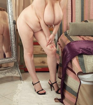 Plump solo girl Micky Bells proudly shows off her giant boobs in the nude