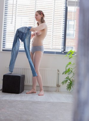 Hidden spy camera captures a solo girl pulling on her panties and blue jeans