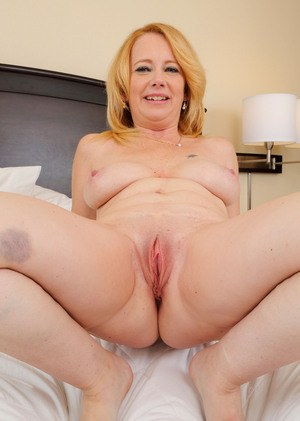 Older blonde plumper Brandie Sweet parts her pink and naked pussy lips