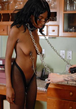 Black female slave licks her mistress' heels during lezdom play in kitchen