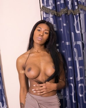 Hot black model Nadia Jay uncovers her nice breasts while disrobing on bed