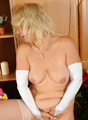 Plump older lady Sara Lynn wears a wide brimmed hat while baring her pussy