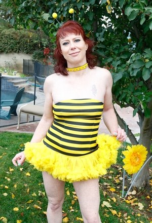 Middle-aged redhead hikes up her bumblebee costume and spreads her cunt lips
