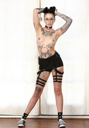 Heavily inked solo model Leigh Raven strips naked with her hair done up