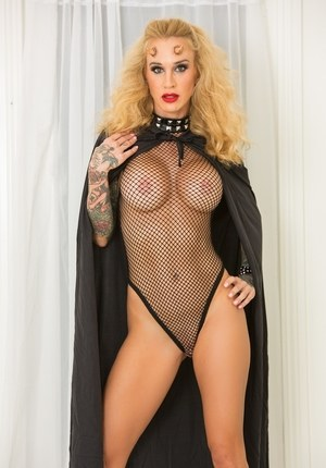 Blond model Sarah Jessie casts her cape aside to pose in mesh onesie and boots
