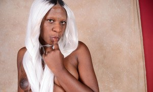 Chunky black female Osa strips naked in a playful way to show her pink pussy