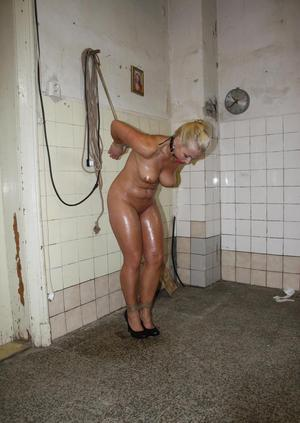 Blond female Veronica struggles with hands tied behind back in unused building