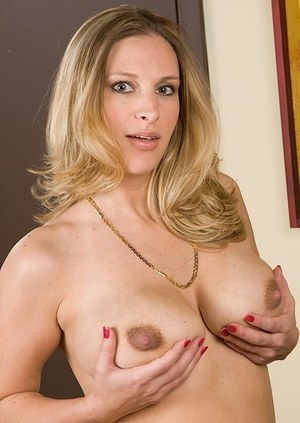 Older blonde MILF Bailyn Stephens cups her big natural tits while undressing
