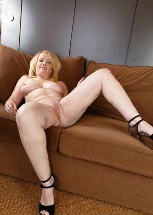 Chunky older lady Brandie Sweet completely undresses for nude posing on sofa