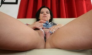 Older brunette lady Louise Bassett fingers her pussy after undressing on couch