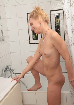 Petite mature lady doffs her bra and panties before wetting her twat in shower
