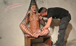 Nude chick is kept confined in a fish net while being masturbated