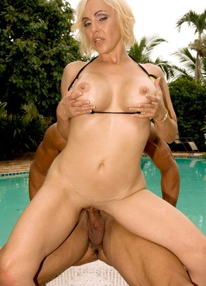 Older blonde Raquel Sieb seduces the Latino pool boy in bikini by the pool