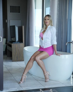 Blonde MILF Audrey Irons undresses before running bath water over her barefeet