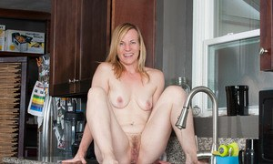 Nude older woman Cody Hunter pees in her kitchen sink after solo masturbation