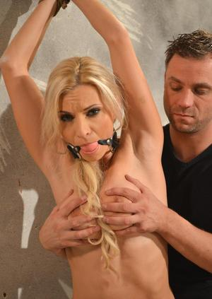 Blonde female has her bare ass spanked with her hands tied above her head