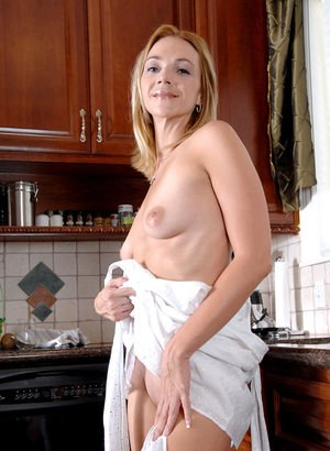 Older woman Samantha runs water over her pussy on kitchen counter