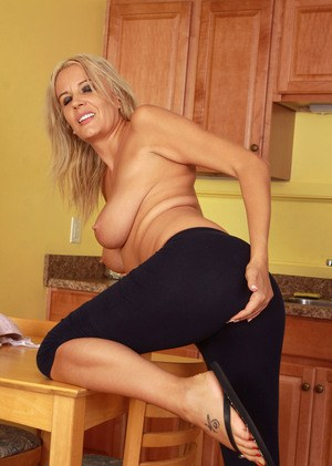 Mature blonde woman disrobes in kitchen before masturbating