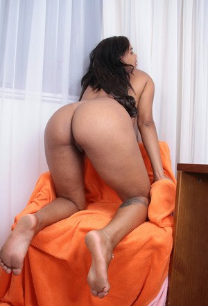 Naked black chick Taiane lays back on a chair and plays with her bald pussy