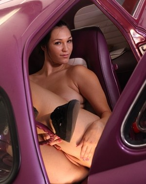 Cute MILF Holly Michaels gets naked for nude posing inside vintage automobile