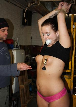 Lena has nipple clamps affixed with her wrists tied above her head and gagged