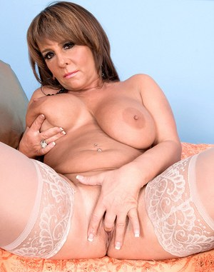 Thick older lady Cassidy bares her big tits before fingering her spread pussy