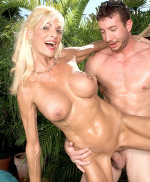 Mature blonde lady Sasha Samuels seduces a younger guy in revealing swimsuit