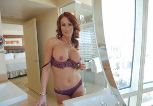 Hot redhead MILF Sabrina Cyns expose her big tits and she gets undressed