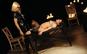 Blonde domme in glasses and latex pours hot candle wax over her lesbian slave