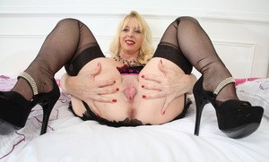 Aged blonde lady Lucinda shows her pink pussy in sexy lingerie and nylons