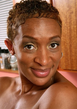 Black female with short hair models naked for first time on kitchen counter