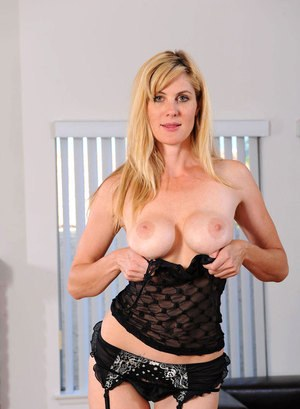 Older blond woman Kate Kastle slips off her black lingerie before masturbating